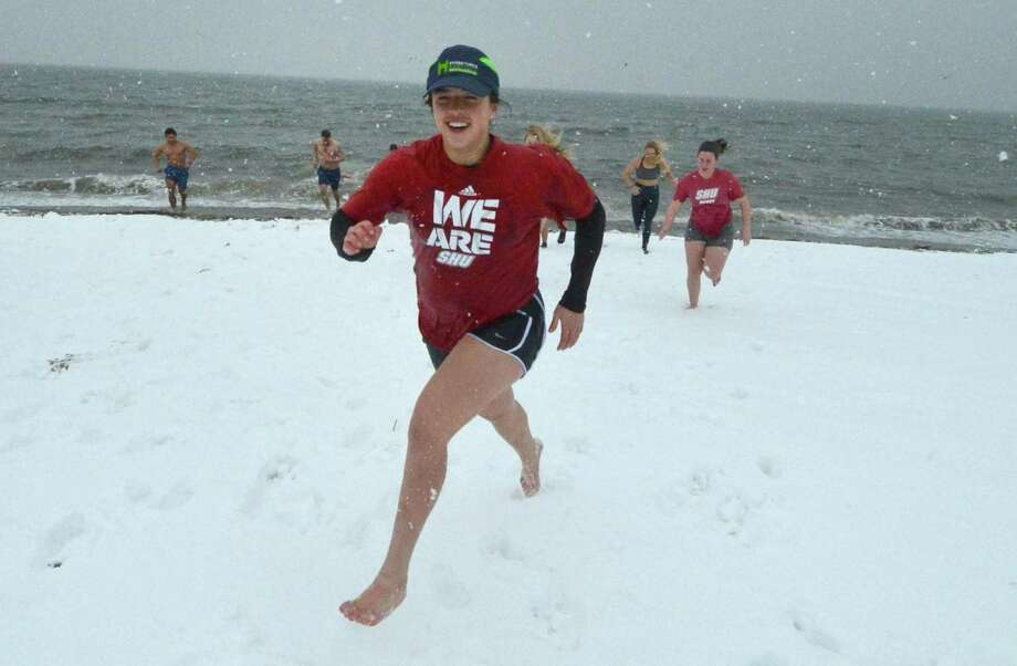 Allie Rinaldi, along with others from the Sacred Heart University Women's Rugby Team, takes part in National Legacy Group's 2nd Annual Rugger Plunge on Feb. 12 at Penfield Beach. With Long Island Sound water temperatures at 36 degrees and blowing snow, about 50 people made the plunge for charity. Photo: Alex Von Kleydorff / Hearst Connecticut Media / Connecticut Post