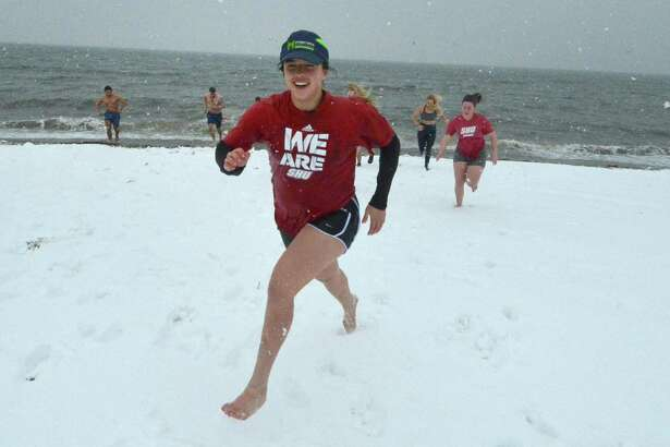 Allie Rinaldi, along with others from the Sacred Heart University Women's Rugby Team, takes part in National Legacy Group's 2nd Annual Rugger Plunge on Feb. 12 at Penfield Beach. With Long Island Sound water temperatures at 36 degrees and blowing snow, about 50 people made the plunge for charity.