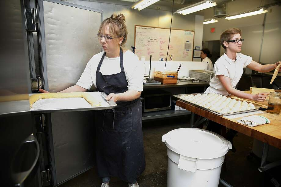 Manresa Bread's Avery Ruzicka (left) cools the rolled dough for the king cake. Photo: Liz Hafalia, The Chronicle