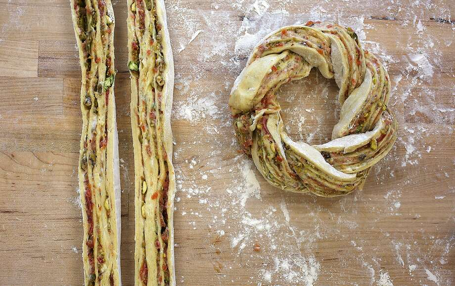 Partner and head baker Avery Ruzicka shows how to twist dough. Photo: Liz Hafalia, The Chronicle