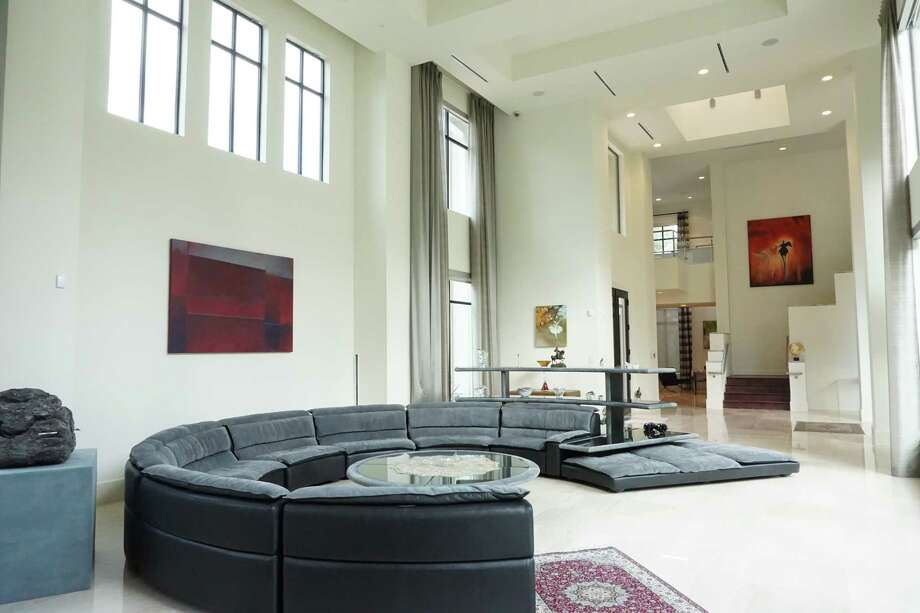 The living room in the Tanglewood home of architect Imad Abdullah and his wife, Dr. Nour Sneige, holds a unique semi-circular sofa that's 18 feet in diameter. It has a matching shelving unit in the back, and a round coffee table with an aquarium set in the middle.. Photo: Gary Zvonkovic/Zvonkovic Photography