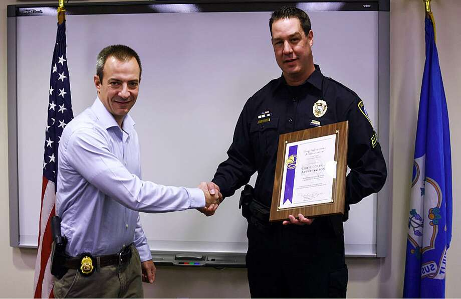 Brian Malagrida, from the Drug Enforcement Administration, thanks Sgt. Jeremiah P. Marron, a Darien detective, for his service on Feb. 7. Photo: Contributed Photo / Darien News