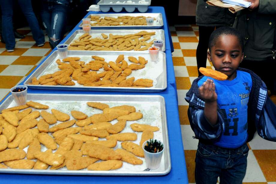 Dean Hunter, a kindergartner who attends Classics Studies Academy, sizes up a chicken tender sample during taste testing of food to be served in Bridgeport Public Schools in Bridgeport, Conn. Feb. 17, 2017. Photo: Ned Gerard / Hearst Connecticut Media / Connecticut Post
