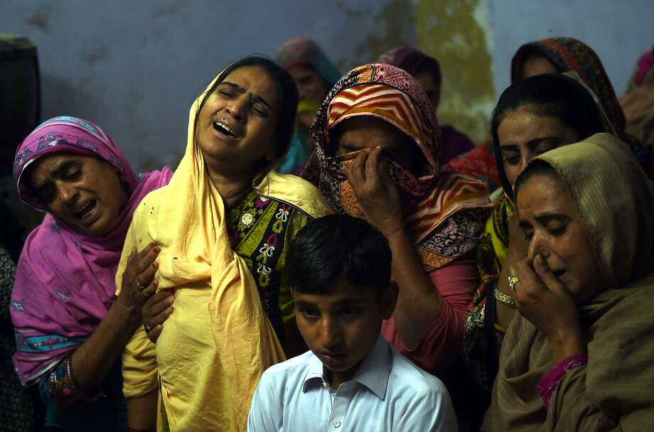 At a funeral for a 13-year-old blast victim, a mother (second from left) mourns over his coffin in Sehwan, Pakistan. Photo: ASIF HASSAN, AFP/Getty Images