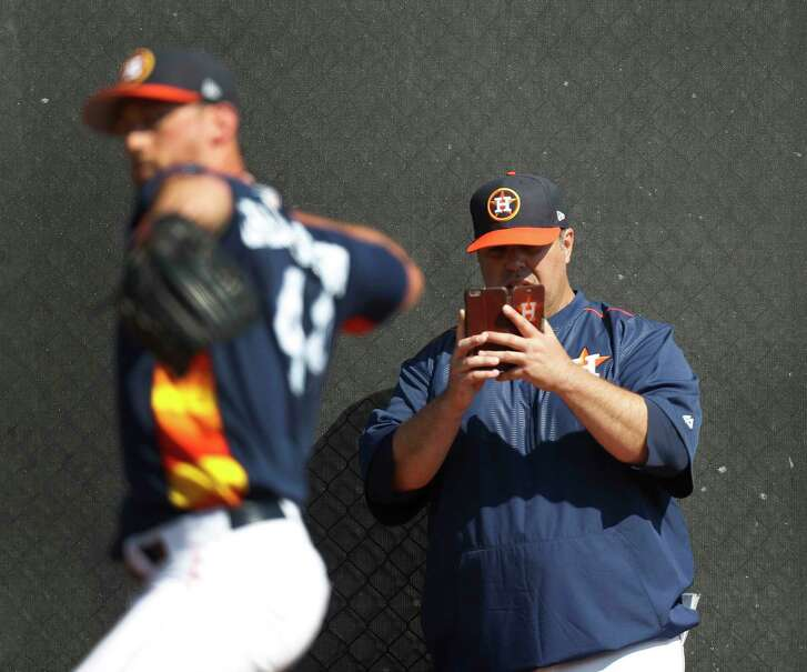 Houston Astros bullpen coach Craig Bjornson takes a photo of pitcher Luke Gregerson as he pitched during spring training at The Ballpark of the Palm Beaches, in West Palm Beach, Florida, Friday, February 17, 2017.
