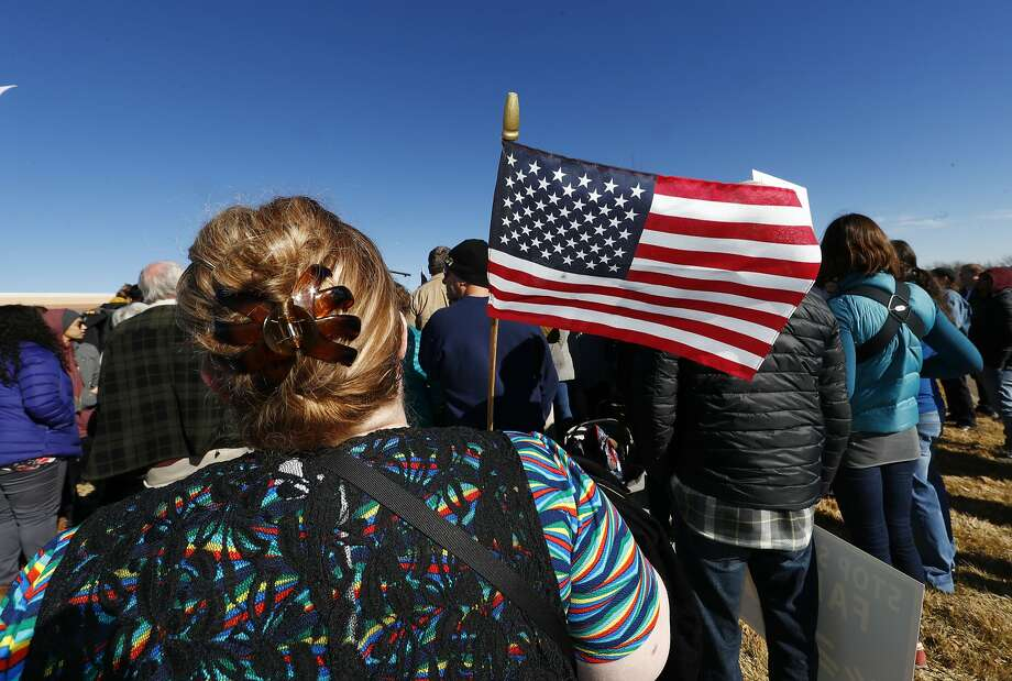 A woman holds an American flag during a rally in support of Jeanette Vizguerra, a Mexican woman seeking to avoid deportation from the United States, outside the Immigration and Customs Enforcement office Wednesday, Feb. 15, 2017, in Centennial, Colo. U.S. immigration authorities have denied Vizguerra's request to remain in the country. (AP Photo/David Zalubowski) Photo: David Zalubowski, Associated Press
