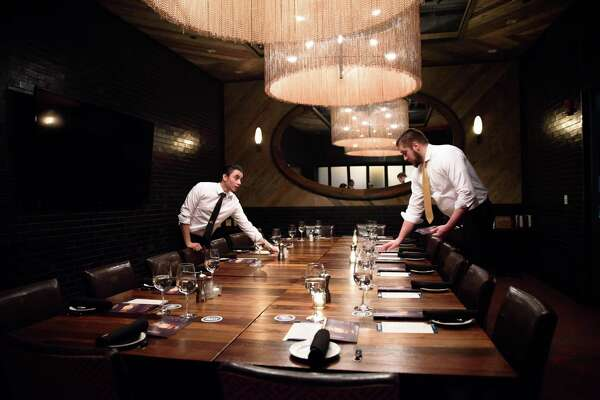 Servers Jesus Aponte and Dan Olsen at Del Frisco's Grille set up for a recent bourbon-themed dinner at the Stamford restaurant.