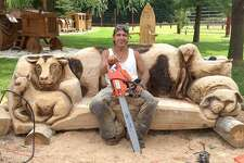 Danbury resident Sergio Atanasoff sits on a farm animal couch he created from wood with his chainsaw.