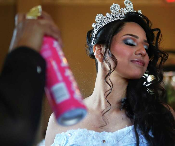 A quinceanera model gets the finishing glitter touches at the My 15 Expo on Sunday, Jan. 22, 2017, in Houston.(Annie Mulligan / Freelance)