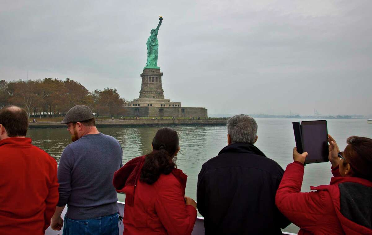 FILE - In this Nov. 5, 2015, file photo, visitors view the Statue of Liberty during a ferry ride to Liberty Island in New York. The travel industry is debating whether President Donald Trump's ban on travel from seven countries will have a larger impact on tourism in the U.S. Some experts say the controversy will have no effect while others worry that it sends an unwelcoming message to travelers around the world. An op-ed piece in the Toronto Star on Jan. 30, 2017, encouraged Canadians to boycott the U.S. for now, saying that the Statue of Liberty will still be there in a few years. (AP Photo/Bebeto Matthews, File) ORG XMIT: NYLS226