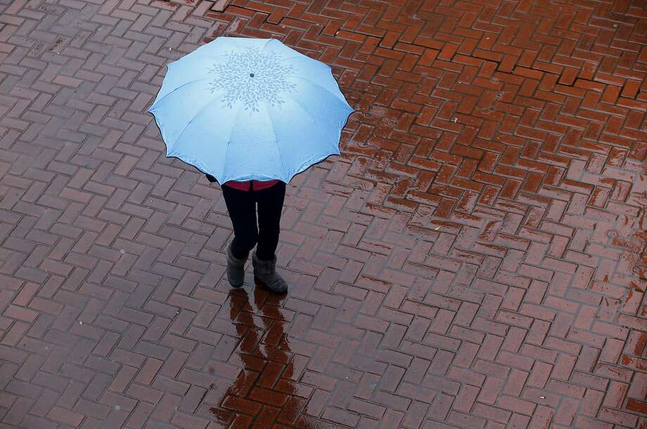 A woman walks through Hallidie Plaza during a recent storm in San Francisco. Photo: Paul Chinn, The Chronicle