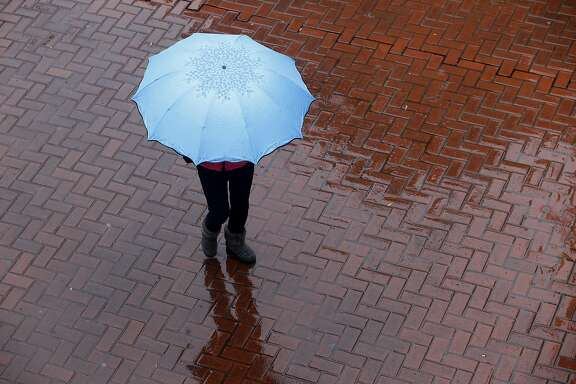 A woman walks through Hallidie Plaza during the heavy wind and rain storm in San Francisco, Calif. on Friday, Feb. 17, 2017.