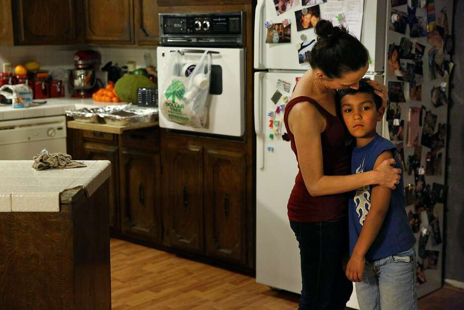 Brittney Barber, who drives for Lyft and Uber, embraces her son, Ethan, the night before she leaves for a stint in San Francisco. Photo: Santiago Mejia, The Chronicle