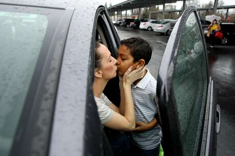 From left: Brittney Barber kisses her son Ethan, 7, as she drops him off at school on Thursday, Feb. 16, 2017 in Clovis, Calif. Barber is driving to Half Moon Bay to stay with a friend and shorten her commute to San Francisco, where she works as a Lyft driver. She''ll be away from home for three days to work 40-50 hours in her grey Honda Fit and then go back home to her family in Fresno County.
