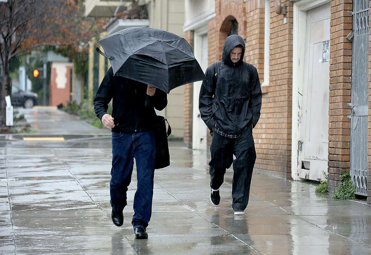 """FILE-- Pedestrians walk down 25th Street in the rain on Friday, February 18, 2017, in San Francisco. A study published Thursday, June 15, 2017, in the journal """"Science"""" suggests that winter snow and rain act as weights on California's mountains, pressing down on both the Sierra and coastal ranges to help bring on earthquakes."""