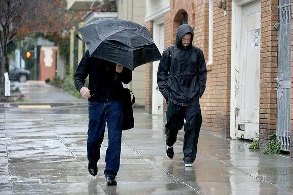 Pedestrians walk down 25th Street in the rain on Friday, February 18, 2017, in San Francisco, Calif.