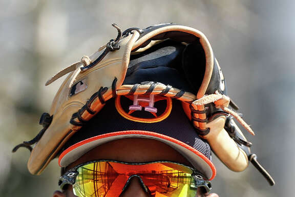 Houston Astros left fielder Tony Kemp (18) wears his glove on his head during spring training at The Ballpark of the Palm Beaches, in West Palm Beach, Florida, Friday, February 17, 2017.