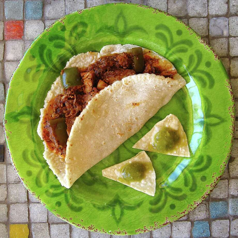 Puerco en chile colorado taco on a handmade corn tortilla from Chile, Tomate y Cebolla. Photo: Mike Sutter /San Anbtonio Express-News