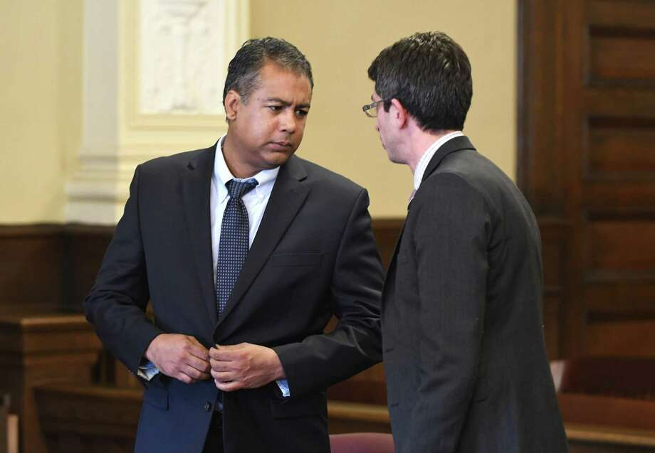 Zarak O. Ali, left, speaks to his attorney Justin V. deArmas, right, in Judge Andrew Ceresia's chambers on Friday, Feb. 17, 2017, in Troy, N.Y. Ali accepted a guilty plea for deed fraud. The plea deal was for an expected aggregate sentence of 3 to 9 year in state prison, concurrent with any sentence out of Albany. He still faces sentences from Saratoga, Schenectady and Columbia Counties. (Will Waldron/Times Union) Photo: Will Waldron / 20039703A