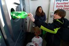 Anthony Dube, 10 of Stamford redeems a bottle with his mother Melissa at the Grade A Market recycling redemption center on Newfield Avenue in Stamford on Feb. 17, 2017. Gov. Dannel P. Malloy has proposed doubling the five-cent deposit on beverages, provoking retailers and environmentalists alike.Environmentalists say the point of the 1980 recycling law was to reduce litter, not generate money from consumers who are too lazy to redeem their cans and bottles.