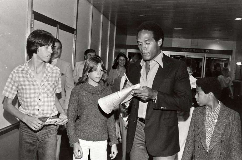 O.J. Simpson (with his son Jason, right) signs autographs at Buffalo International Airport in 1980. Photo: Courtesy Of ESPN Films / Courtesy of ESPN Films