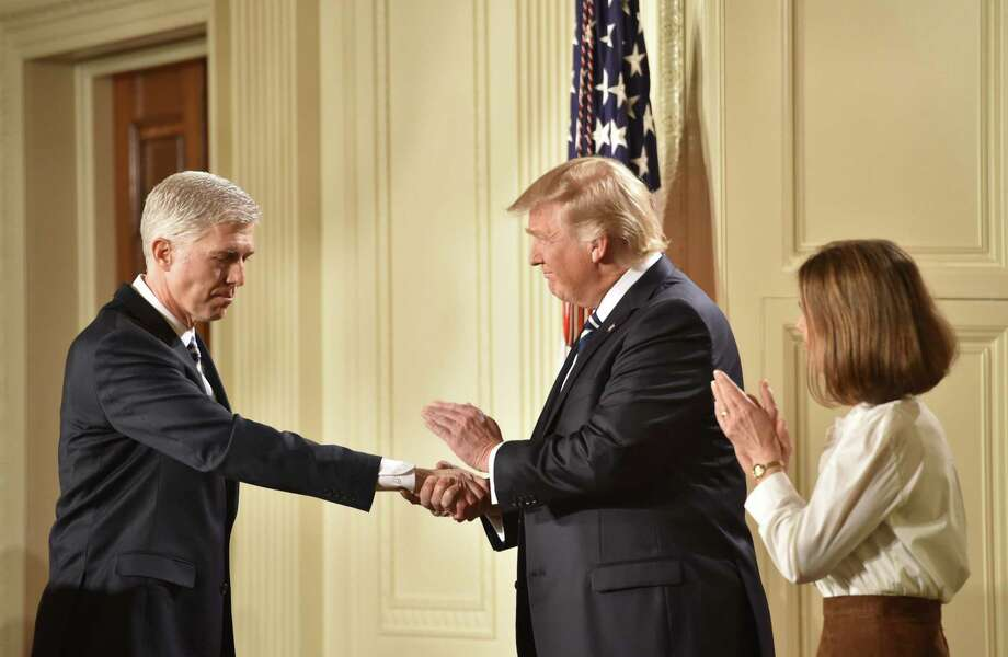 Judge Neil Gorsuch shakes hands with President Donald Trump after he was nominated for the Supreme Court on Jan. 31. His nomination has sparked a political battle that largely ignores that a judge's duty is to simply interpret the law. Photo: Nicholas Kamm /AFP /Getty Images / AFP or licensors