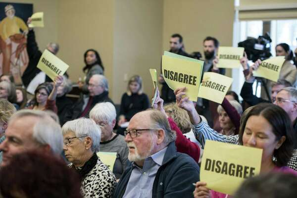 Crowd members use signs to voice their opinions during Republican Rep. Jim Sensenbrenner's town hall meeting at in Pewaukee, Wis., on Feb. 11. Town halls for GOP Congress members are reminiscent of tea party behavior in 2009.