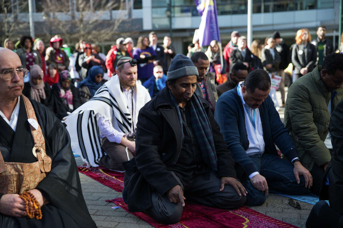 """Protesters hold a """"pray in"""" during Amazon's lunch hour to urge the tech-giant to give all workers a fair and consistent prayer policy."""