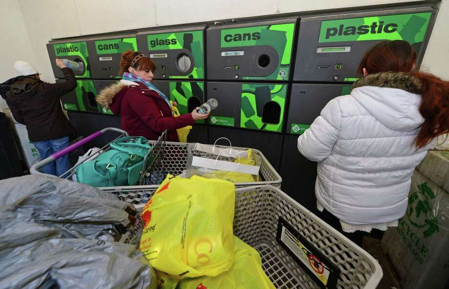 LInda Cerratio, center, and her daughter, Karissa, right, return bottles and cans to redeem the five-cent deposit at Stop and Shop on Connecticut Avenue Friday, February 17, 2017, in Norwalk, Conn. Connecticut Gov. Dannel P. Malloy has proposed doubling the five-cent deposit on beverages, provoking retailers and environmentalists alike. Environmentalists say the point of the 1980 recycling law was to reduce litter, not generate money from consumers who are too lazy to redeem their cans and bottles. Photo: Erik Trautmann / Hearst Connecticut Media / Norwalk Hour
