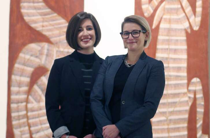 Curators Lana Meador (left) and Erin Murphy pose in front of two paintings that are on display as part of a contemporary Aboriginal art show at the San Antonio Museum of Art.