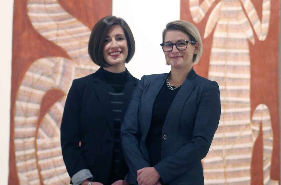 Curators Lana Meador (left) and Erin Murphy pose in front of two paintings that are on display as part of a contemporary Aboriginal art show at the San Antonio Museum of Art. Photo: William Luther /San Antonio Express-News / © 2017 San Antonio Express-News