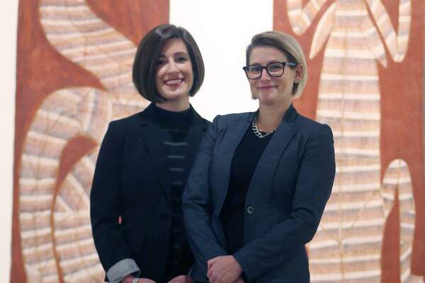 Curators Lana Meador and Erin Murphy pose in front of two paintings that are on display as part of a contemporary Aboriginal art show at the San Antonio Museum of Art.
