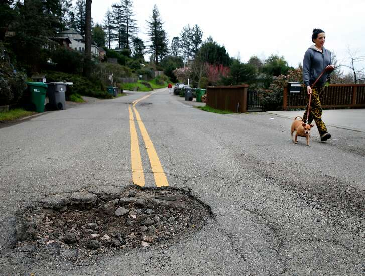 A neighbor walks her dog past a large pothole in the middle of Broadway Terrace in Oakland, Calif. on Wednesday, Feb. 15, 2017. Street maintenance crews are struggling to keep up with a large number of potholes due to the constant rain.