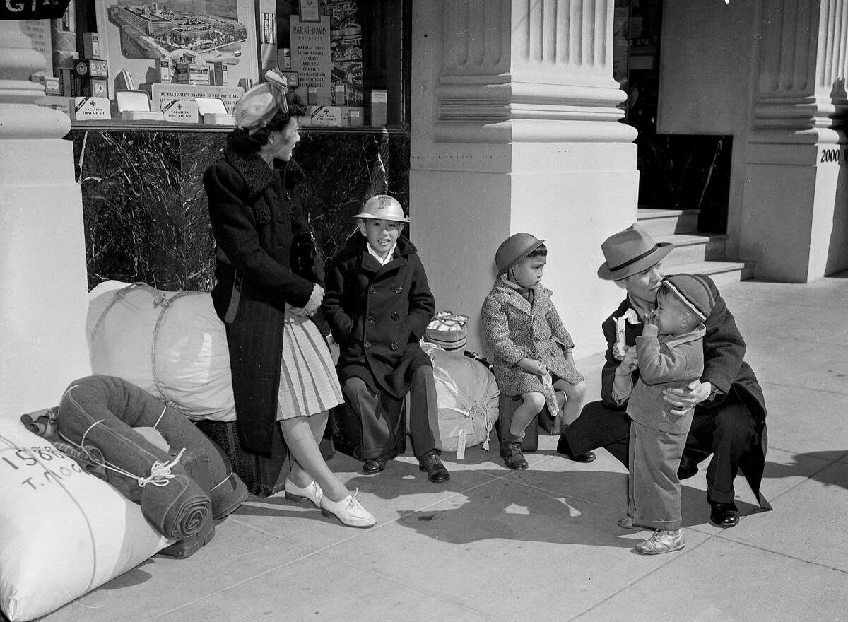 June 1942: A San Francisco family of Japanese descent waits near the SFPD Northern Station, before heading to a U.S. internment camp during World War II.