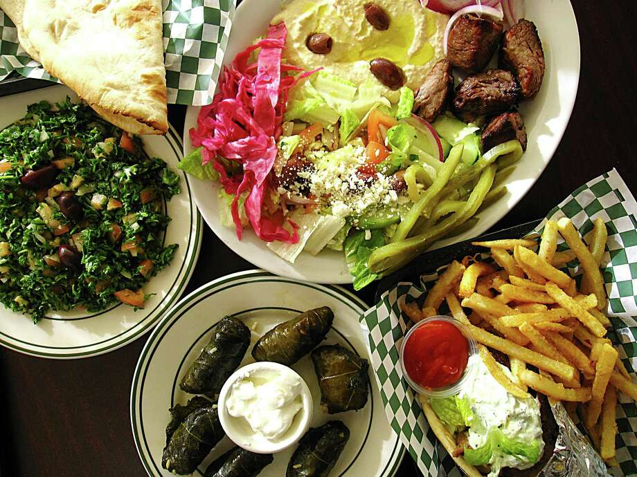 A sampler of dishes from Atlas Mediterranean Grill, a new restaurant on San Pedro Avenue. Clockwise from left: tabbouleh, beef tikkah plate with pita and hummus and salad, a beef-and-lamb gyro wrap with fries and a plate of stuffed grape leaves. Photo: Mike Sutter /San Antonio Express-News