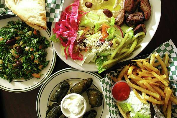 A sampler of dishes from Atlas Mediterranean Grill, a new restaurant on San Pedro Avenue. Clockwise from left: tabbouleh, beef tikkah plate with pita and hummus and salad, a beef-and-lamb gyro wrap with fries and a plate of stuffed grape leaves.