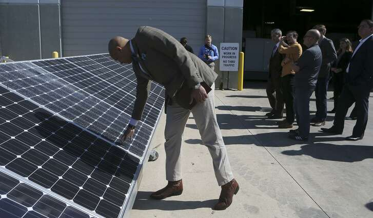 District 2 City Councilman Alan Warrick II checks out a solar panel during Friday's tour of Kaco New Energy. The company makes solar power inverters for utility, commercial and residential customers.
