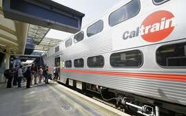 FILE  - In this July 1, 2013, file photo, commuters board a Caltrain train at the Caltrain and Bay Area Rapid Transit station in Millbrae, Calif. The Federal Transit Administration is delaying a decision on whether to approve a $650 million federal grant for electrification of a San Francisco Bay Area train system that would also help California's high-speed rail project. Congressional Republicans had pushed the administration to reject the application from Caltrain. (AP Photo/Jeff Chiu, File)