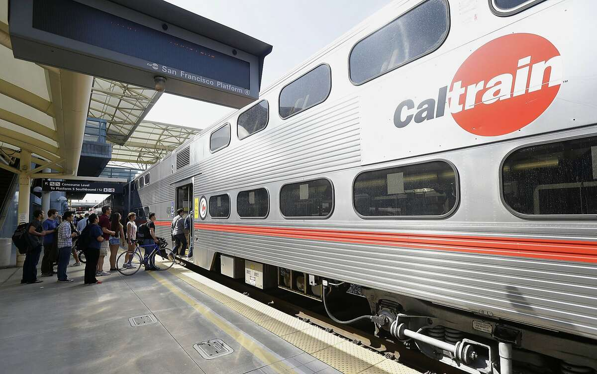 In this July 1, 2013, file photo, commuters board a Caltrain train at the Caltrain and Bay Area Rapid Transit station in Millbrae, Calif. Caltrain recently approved the 2040 Service Vision plan, which looks to dramatically increase the number of trains moving through stations. >> Keep clicking through the slideshow to look at the new electrified Caltrain cars.