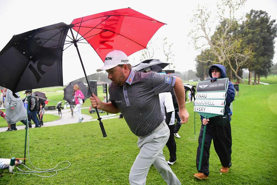Graeme McDowell heads the for clubhouse as play is called. Photo: Harry How, Getty Images