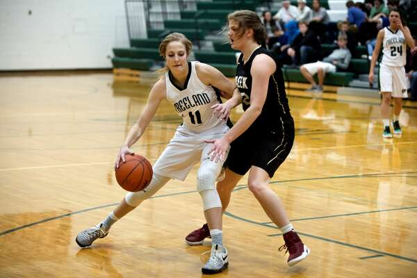 BRITTNEY LOHMILLER   blohmiller@mdn.net Freeland's Jenna Gregory, left, dribbles around Bullock Creek's Baleigh Hill in the first half of the Friday evening game at Freeland High School. Freeland defeated Bullock Creek 68-25 and remain undefeated.