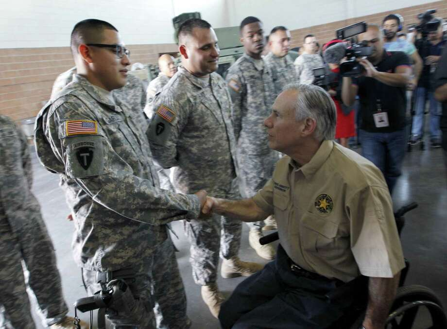 Texas Gov. Greg Abbott shakes Texas National Guard Spc. Jesus Garza after a briefing on their border security mission, Wednesday, Dec. 23, 2015 at the National Guard Armory in Weslaco, Texas. (Nathan Lambrecht/The Monitor via AP) Photo: Nathan Lambrecht, MBO / Associated Press / The Monitor