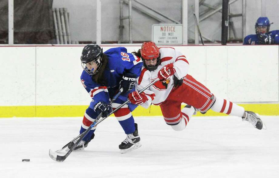 Fairfield Ludlowe/Warde's Sarah Powlishen (16), left, with the puck, is taken down by an airborne Emily Bello of Greenwich during the girls ice hockey game at Hamill Rink in Greenwich on Feb. 14. Bello was called for a penalty on the play. Photo: Bob Luckey Jr. / Hearst Connecticut Media / Greenwich Time