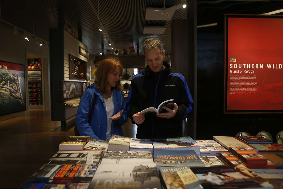 Joan Brown (left) and husband, Gary, tourists from Virginia, examine a book about San Francisco as they check out the new Presidio Visitors Center. Photo: Natasha Dangond, The Chronicle