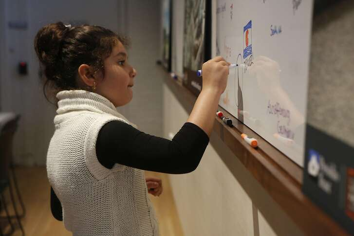 Aleyna Tokdemir draws an ocean on a white board inside Presidio Visitors Center on Friday, Feb. 17, 2017, in San Francisco, Calif.
