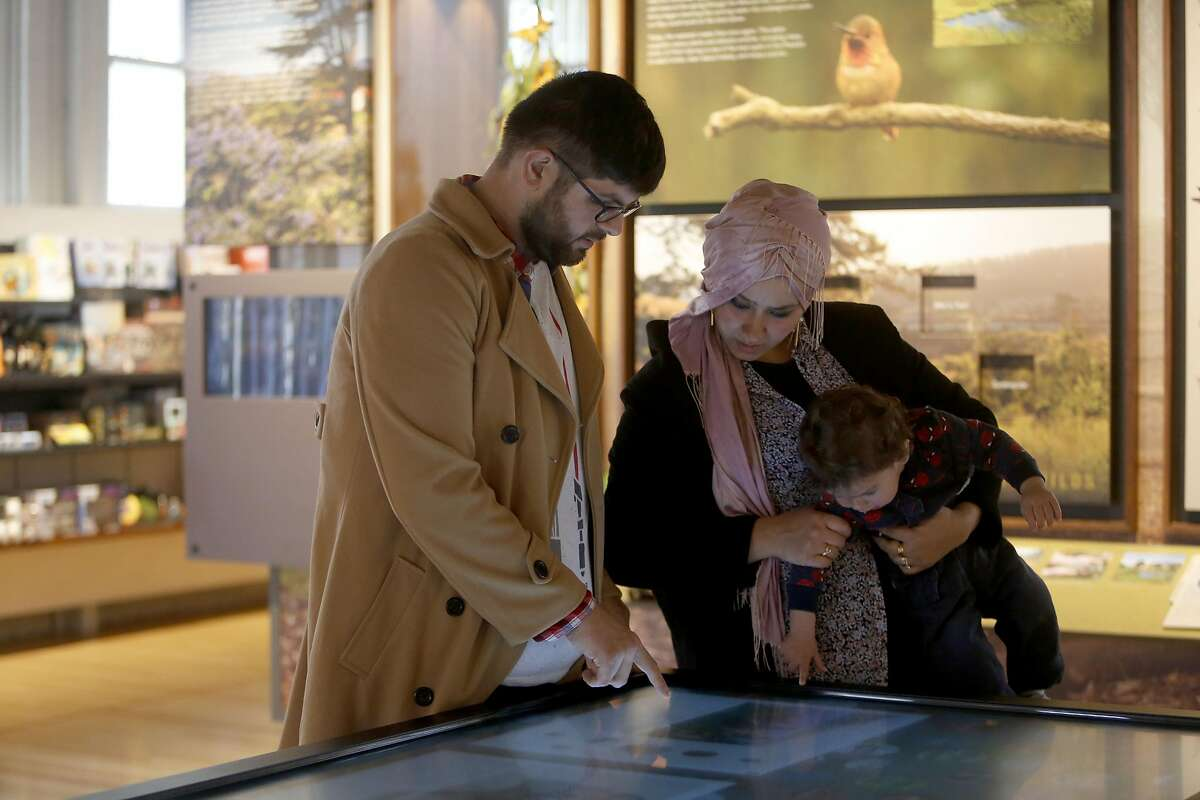 Mikayil Tokdemir, left, looks at an interactive touch screen with his wife, Fatmagul, and his son Ahmet on Friday, Feb. 17, 2017, in San Francisco, Calif.