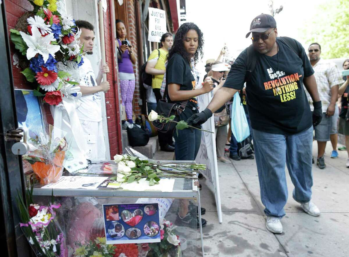 FILE - In this July 17, 2015 file photo, a man places a rose on a memorial for Eric Garner during a rally at the site of his fatal encounter with police in the Staten Island borough of New York. A federal investigation of the police chokehold death of Garner is moving forward in New York, but its future could be up in the air as a new U.S. attorney general with a law-and-order bent takes over the Justice Department. The federal grand jury in Brooklyn met as late as last week to hear evidence in the deadly confrontation on Staten Island in 2014, which helped fuel a national outcry over killings of unarmed black men by police officers. (AP Photo/Mary Altaffer, File) ORG XMIT: NYR303