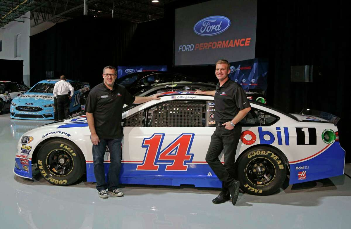 FILE - In this Jan. 18, 2017, file photo, team owner Tony Stewart, left, and driver Clint Bowyer pose for a photo during a news conference in Concord, N.C. Bowyer gets his first ride in a brand new shiny Ford Fusion, one adorned with Stewart's beloved No. 14 on the side, when practice for the Daytona 500 begins on Saturday. (AP Photo/Chuck Burton, File) ORG XMIT: NY171