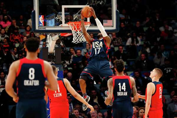 U.S. guard Jonathon Simmons of the San Antonio Spurs dunks in front of World guard Dante Exum (11) of the Utah Jazz and Nikola Jokic (15) of the Denver Nuggets during the Rising Stars Challenge as part of the NBA All-Star events in New Orleans, Friday, Feb. 17, 2017. (AP Photo/Gerald Herbert)
