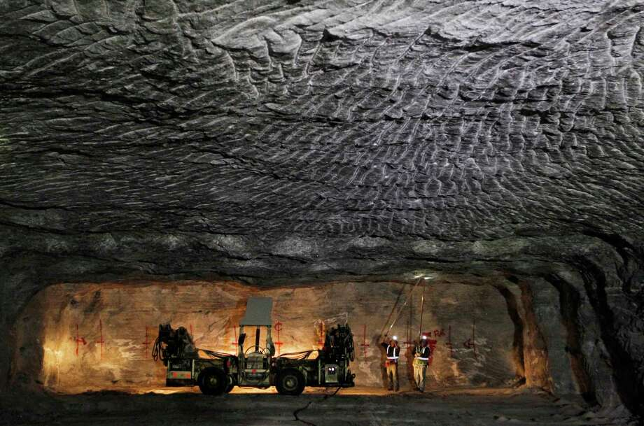 In this Jan. 27, 2017 photo, American Rock Salt Co. workers use hand scalers to remove loose roof material at the mine in Hampton Corners, N.Y. Deep below upstate New York's farm country, workers in ghostly tunnels are praying for snow. Fiercer winters mean better business, longer hours and fatter paychecks at what's billed as the nation's most productive salt mine, which ships trainloads of snow-melting road salt to municipalities across the Northeast. (AP Photo/Jeffrey T. Barnes) ORG XMIT: NYJB101 Photo: Jeffrey T. Barnes / 2017